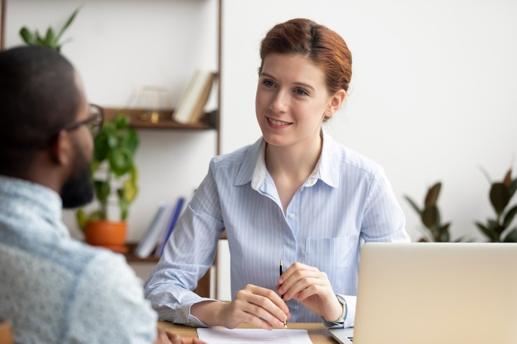 Smiling hr manager listening to african job seeker at interview