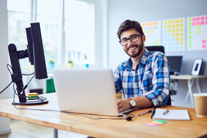 Cheerful young programmer looking at camera while working at his office