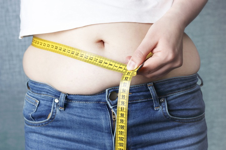 Woman's hand measure her stomach with a tape measures, overweight concept