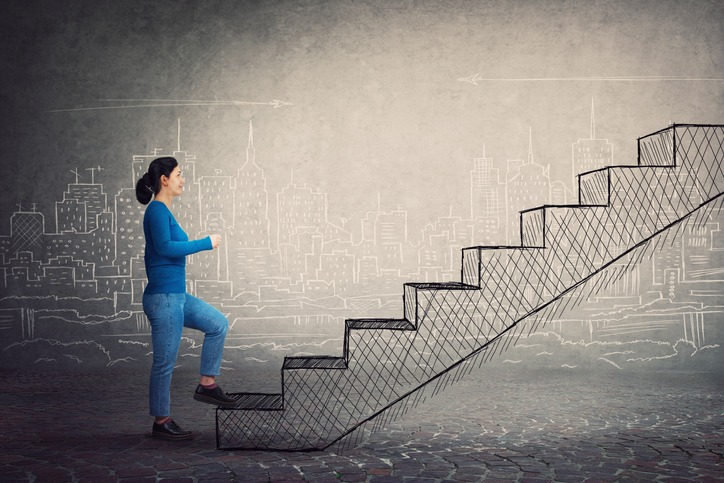 Motivated and confident young woman hurry to climb a imaginative staircase. Concept of career development, success and goal achievement. Casual girl rush, making a big step.