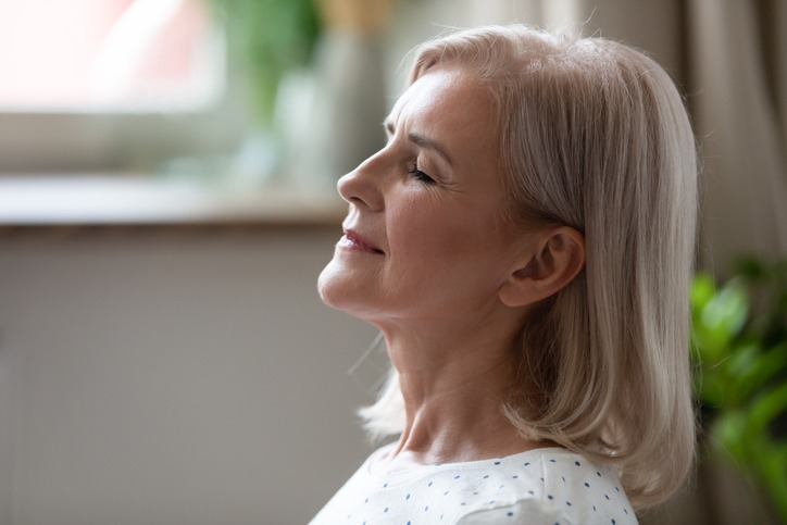 Calm serene middle aged woman breathing with eyes closed