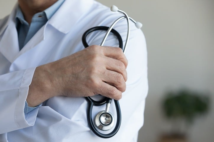 Senior male doctor holding stethoscope in hand, close up view