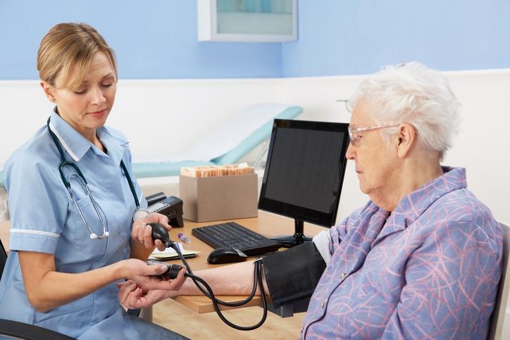 UK nurse taking senior woman's blood pressure