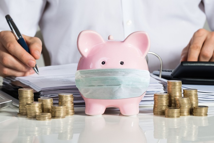 Businessman Calculating Invoice With Piggybank And Coins At Desk