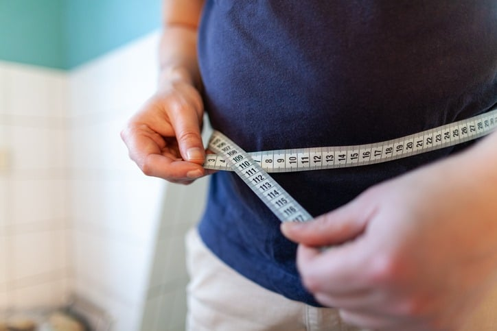 man measures her abdomen with a measuring tape