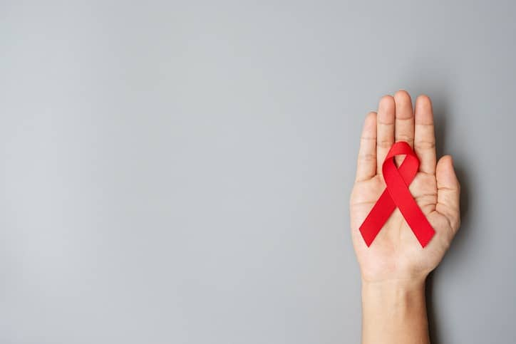 Hand holding Red Ribbon for supporting people living and illness. Healthcare and safe sex concept. December World Aids Day and multiple myeloma Cancer Awareness month
