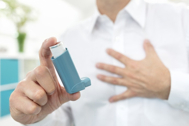 Man using blue asthma inhaler medication