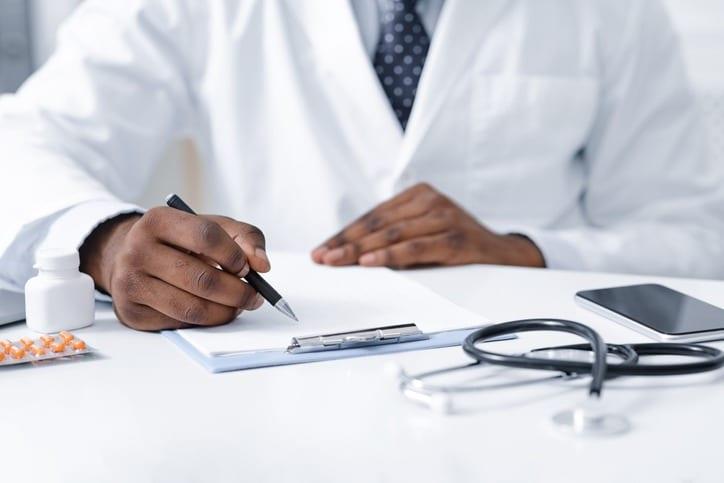 Close up of african doctor prescribing pills to patient