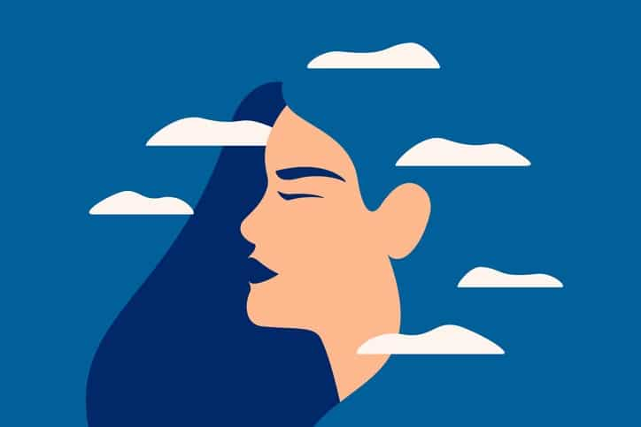 A sad young woman has a clouded mind on blue background.