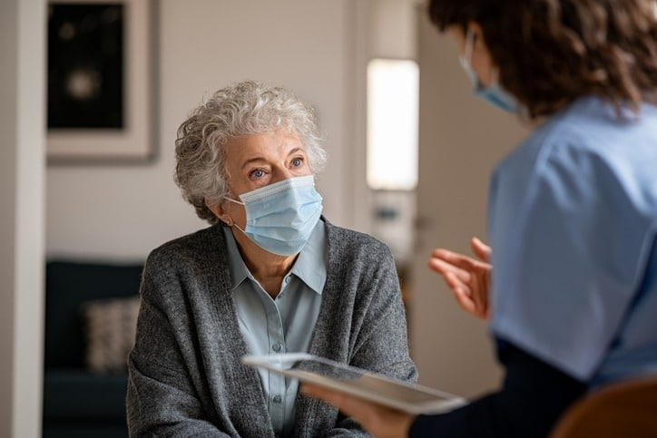 Doctor home visit a senior woman during the covid-19 pandemic