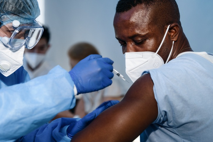 african americam man looking at coronavirus covid-19 syring when medical staff injecting vaccine to arm muscle to build immunization of coronavirus covid-19 for him