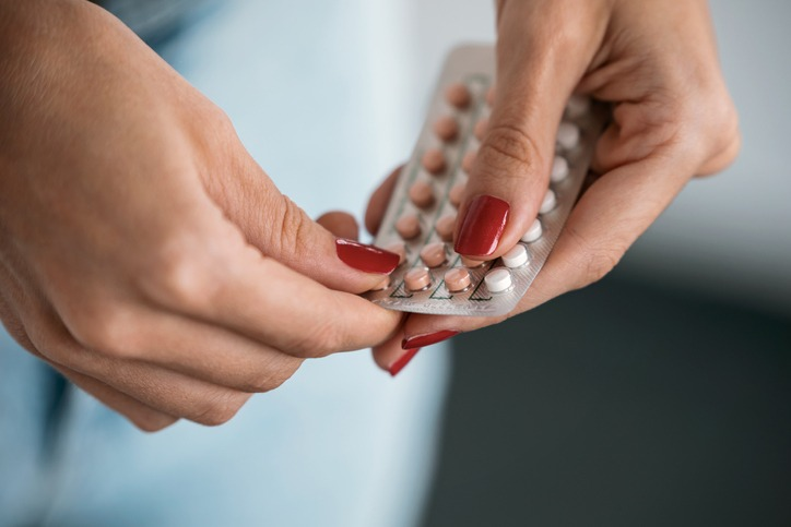 Woman holding a contraceptive pills. Concept of contraception methods.