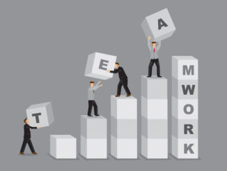 A team lifting blocks that say 'teamwork' and handing them to one another