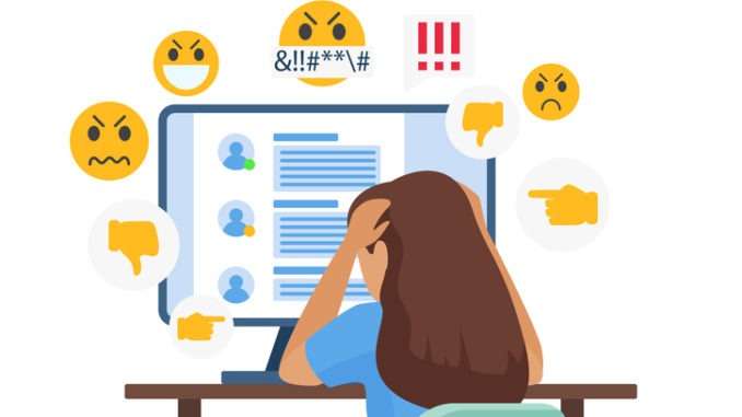 A person looks at a computer with their head in their hands. Negative emojis surround them.