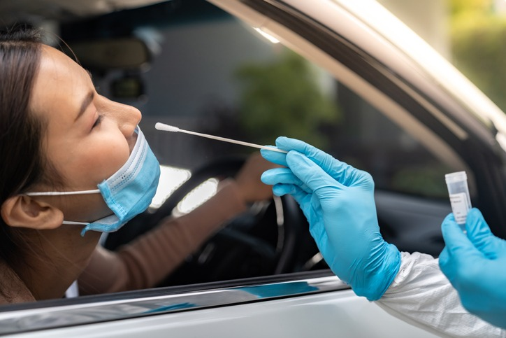 Asian woman Drive Thru COVID-19 testing with PPE medical staff