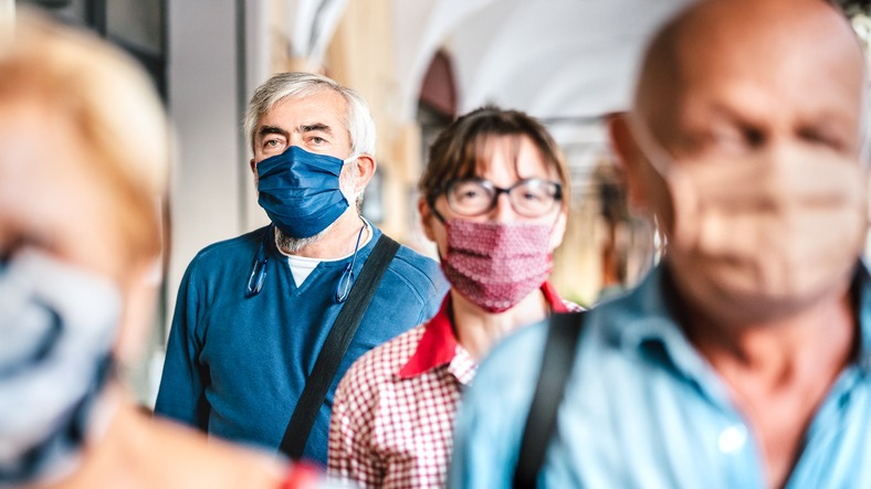 Crowd of adult citizens walking on city street – New reality lifestyle concept with senior people with covered faces – Selective focus on bearded man with blue protective mask