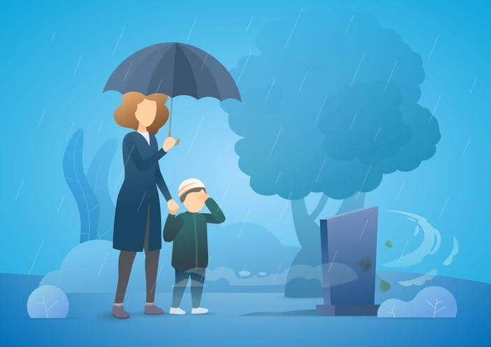 Sad woman with son grieving in a cemetery. Woman standing at the gravestone of her beloved husband. Rainy day. Family member death from the coronavirus.